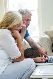 Couple de personnes âgées graves à l'aide d'un ordinateur portable à la maison