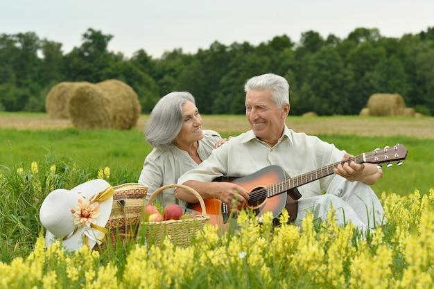 Couple de personnes âgées avec guitare au champ d'été avec des fleurs
