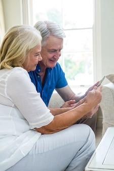 Couple de personnes âgées heureux à l'aide d'une tablette numérique à la maison