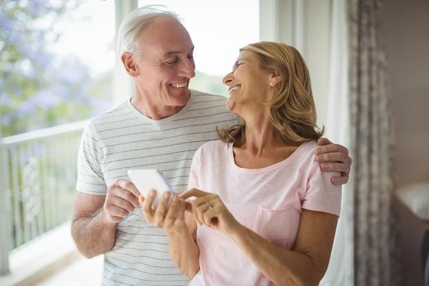 Couple de personnes âgées heureux à l'aide de téléphone mobile dans le balcon