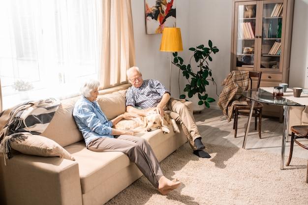 Couple de personnes âgées heureux avec chien à la maison