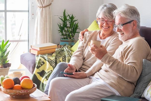 Couple de personnes âgées heureux et insouciant se relaxant à la maison sur le canapé en buvant une tasse de thé