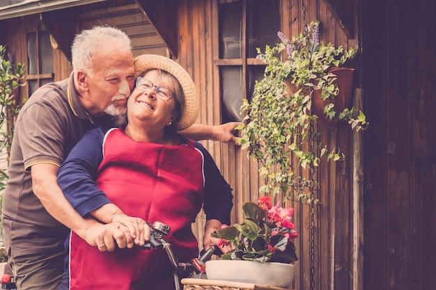 Un couple de personnes âgées heureux s'amuse en plein air à la maison dans le jardin - un homme et une femme mûrs et joyeux sourient et rient dans un style de vie joyeux - personnes âgées caucasiennes et bonheur