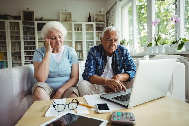 Couple de personnes âgées inquiet à l'aide d'un ordinateur portable