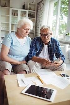 Couple de personnes âgées inquiet vérifiant les factures