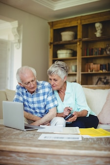 Couple de personnes âgées inquiet, vérification des factures dans le salon
