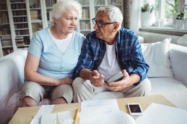 Couple de personnes âgées inquiets interagissant tout en vérifiant les factures