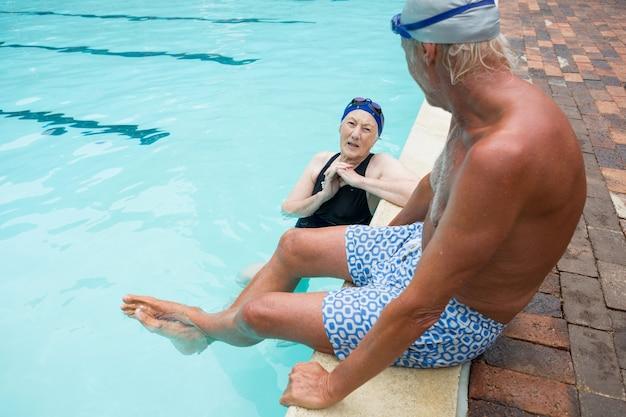 Couple de personnes âgées interagissant les uns avec les autres au bord de la piscine