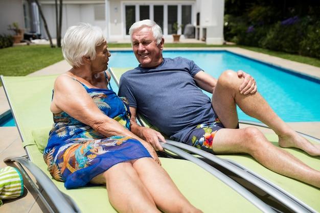 Couple de personnes âgées interagissant les uns avec les autres sur une chaise longue au bord de la piscine