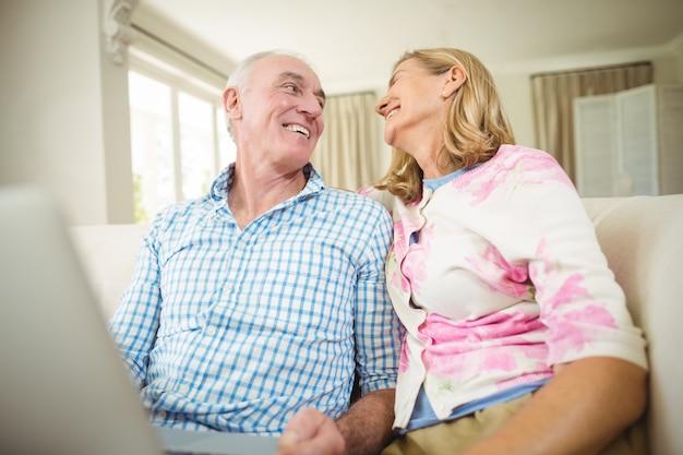 Couple de personnes âgées interagissant les uns avec les autres tout en utilisant un ordinateur portable dans le salon
