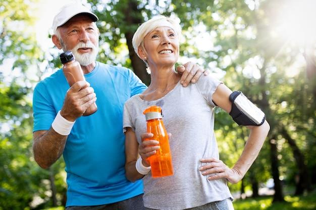 Couple de personnes âgées jogging et courir à l'extérieur dans la nature du parc