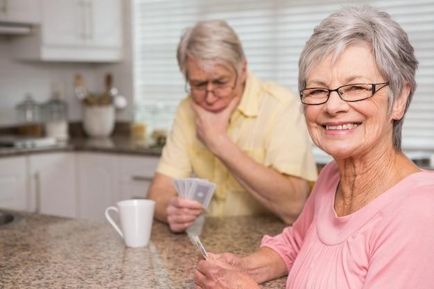 Couple de personnes âgées jouant aux cartes au comptoir