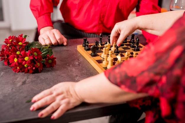 Couple de personnes âgées jouant aux échecs
