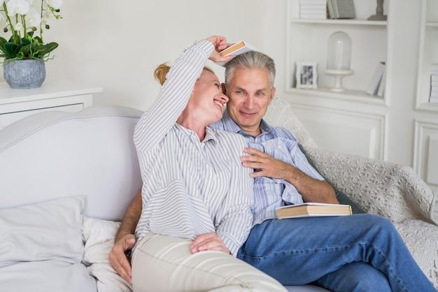 Couple de personnes âgées jouant avec des livres
