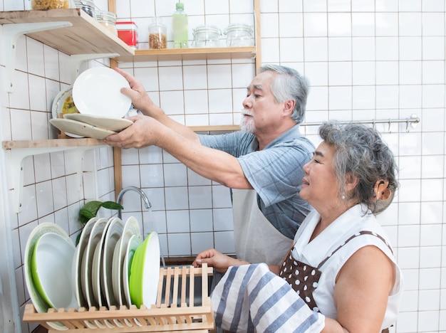 Couple de personnes âgées, laver la vaisselle dans la cuisine à la maison.