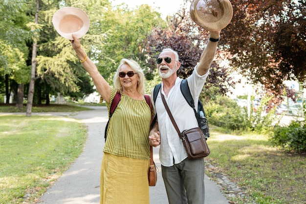 Couple de personnes âgées levant leur chapeau en l'air