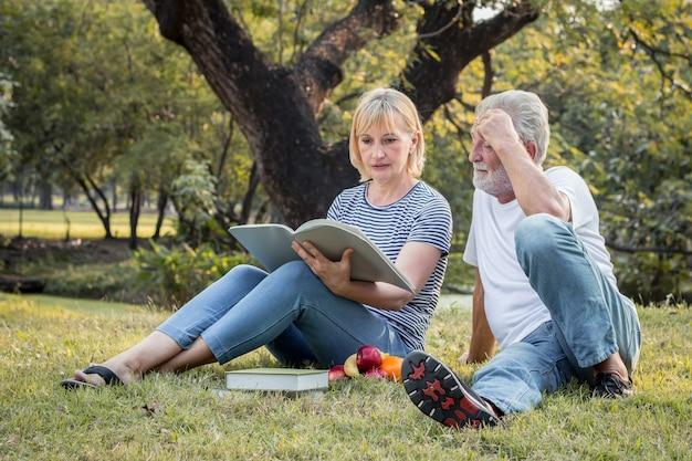 Couple de personnes âgées lisant ensemble dans le parc le matin.
