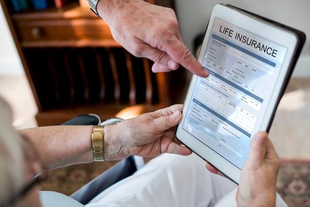 Couple de personnes âgées en lisant le formulaire d'assurance-vie en comprimé
