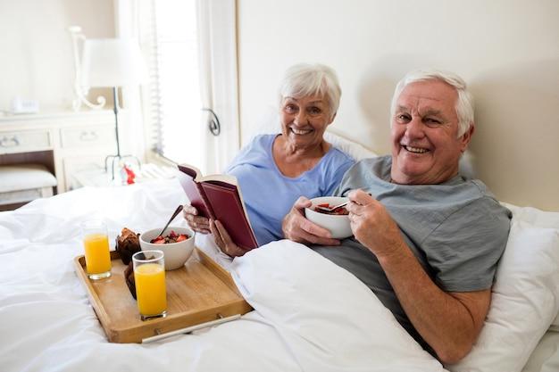 Couple de personnes âgées lisant un livre tout en prenant le petit déjeuner dans la chambre à la maison