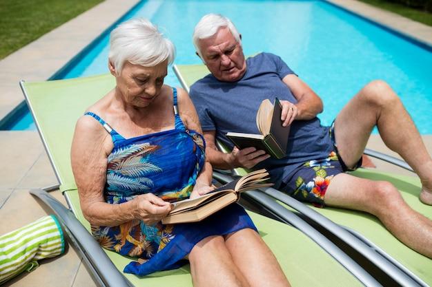 Couple de personnes âgées lisant des livres sur une chaise longue au bord de la piscine