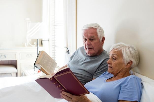 Couple De Personnes âgées Lisant Des Livres Dans La Chambre à La Maison Photo Premium