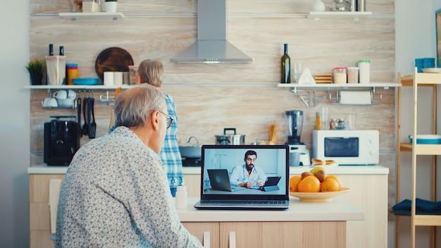 Couple de personnes âgées lors d'une vidéoconférence avec un médecin utilisant un ordinateur portable dans la cuisine pour discuter de problèmes de santé. consultation de santé en ligne pour personnes âgées médicaments maladie conseil sur les symptômes, médecin tel