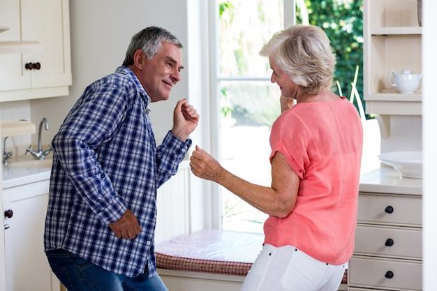 Couple de personnes âgées ludique dansant dans la cuisine