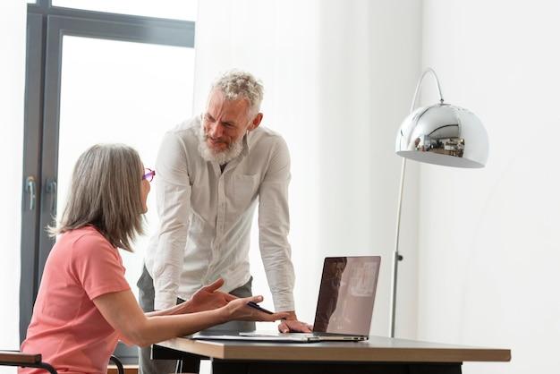 Couple de personnes âgées à la maison à l'aide d'un ordinateur portable