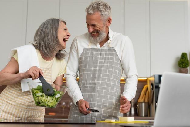 Couple de personnes âgées à la maison dans la cuisine prenant des cours de cuisine sur ordinateur portable