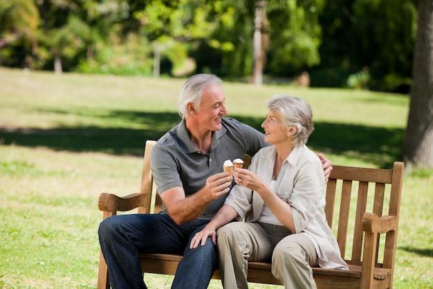 Couple de personnes âgées mangeant une glace sur un banc