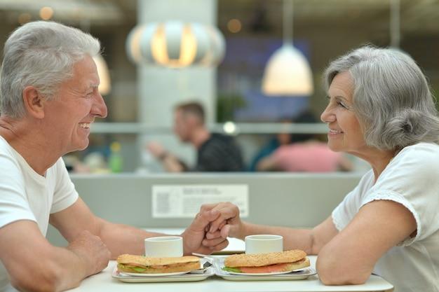 Couple de personnes âgées mangeant de la restauration rapide