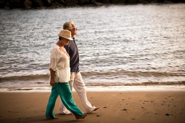 Couple de personnes âgées marchant au bord de la mer