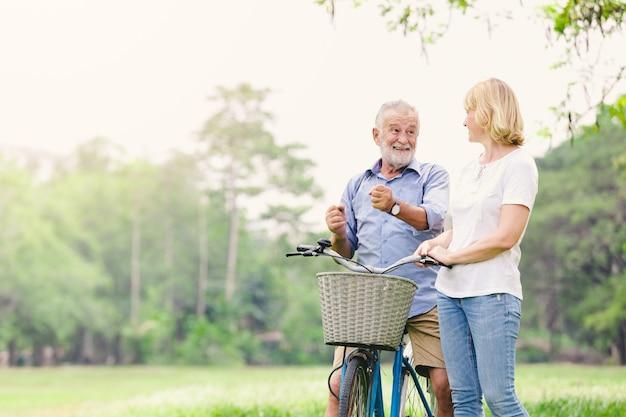 Couple de personnes âgées marchant leur vélo