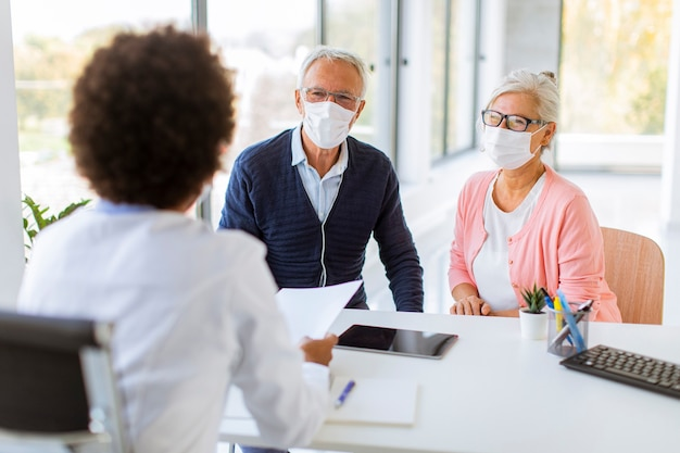 Un couple de personnes âgées avec des masques faciaux de protection reçoit des nouvelles d'une femme médecin noire au bureau