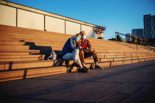 Couple de personnes âgées avec des masques protecteurs sur assis sur les escaliers et câlins.