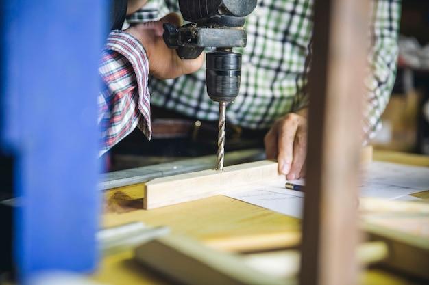 Couple de personnes âgées méconnaissable forant une latte en bois dans leur atelier