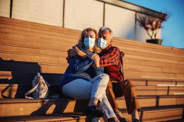 Couple de personnes âgées mignon avec des masques chirurgicaux protecteurs assis sur les escaliers à l'extérieur et étreindre.