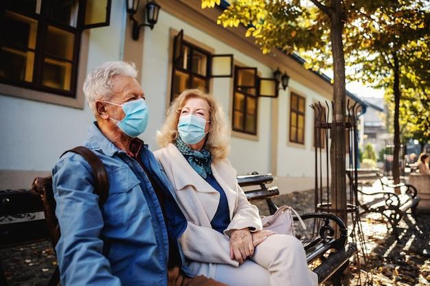 Couple de personnes âgées mignon avec des masques de protection assis sur le banc à l'extérieur et bavarder.