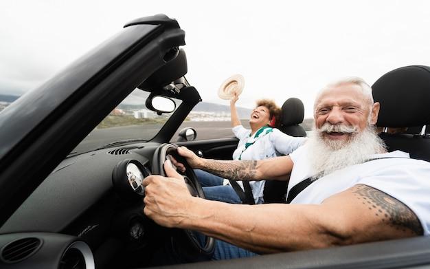 Couple de personnes âgées à la mode s'amusant dans une voiture décapotable pendant les vacances d'été