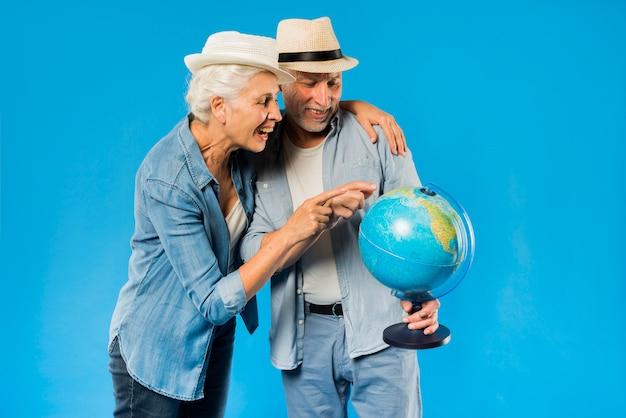 Couple de personnes âgées moderne avec globe