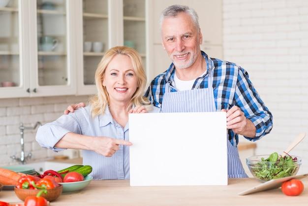 Couple de personnes âgées montrant une pancarte vierge blanche sur une table en bois dans la cuisine