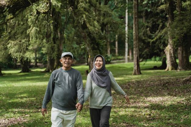 Couple de personnes âgées musulmanes marchant ensemble dans le jardin