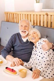 Couple de personnes âgées optimiste en levant et posant au café