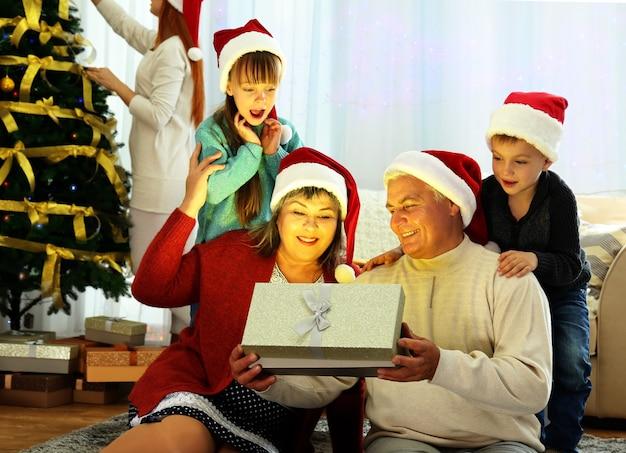 Couple de personnes âgées ouvrant le cadeau de noël dans le salon