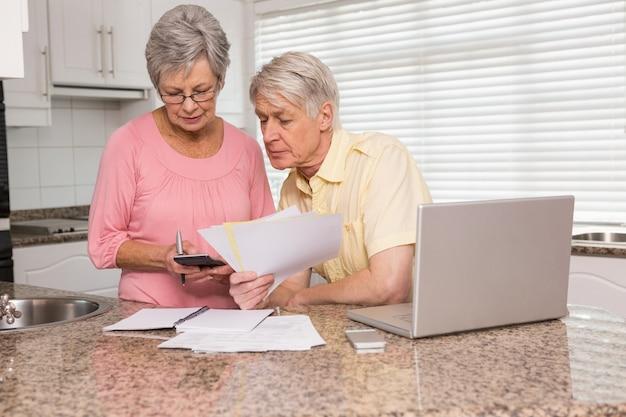 Couple de personnes âgées paient leurs factures avec un ordinateur portable