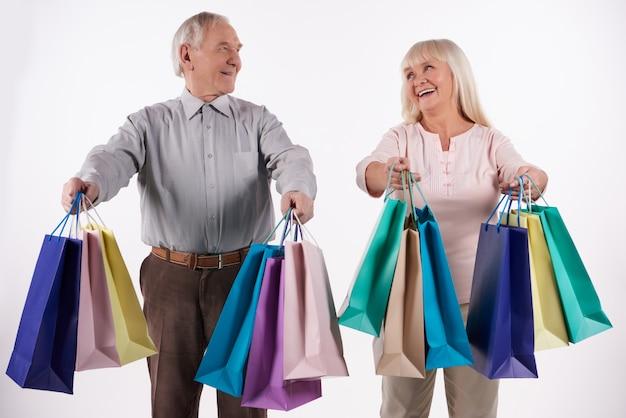 Couple de personnes âgées avec des paquets vont faire les courses.