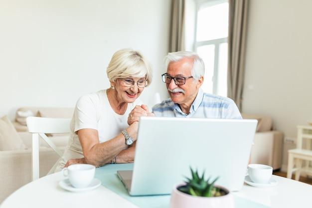Couple de personnes âgées parle en ligne via une connexion vidéo sur l'ordinateur portable