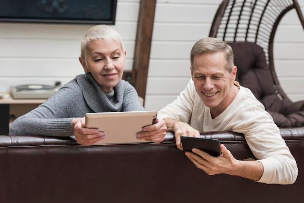 Couple de personnes âgées passer du temps ensemble sur leurs appareils