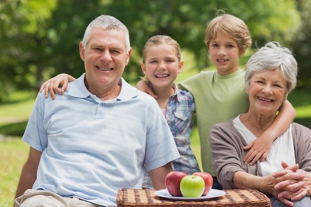 Couple de personnes âgées et petite-fille avec panier de pique-nique au parc