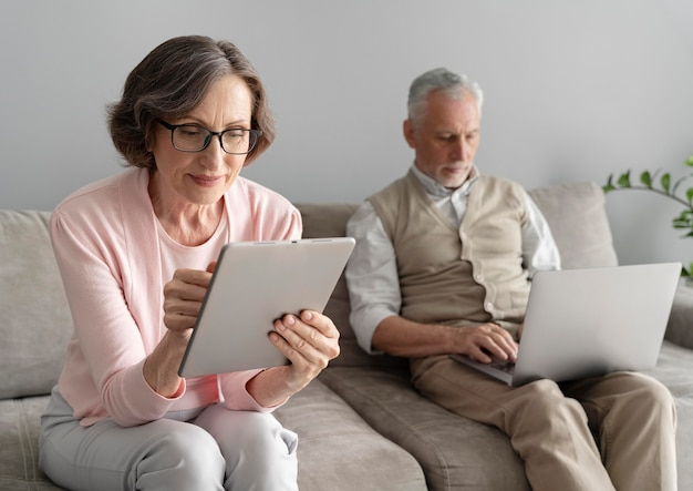 Couple de personnes âgées à plan moyen avec des appareils